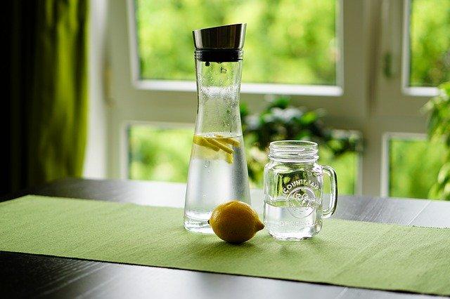 水にスライスレモンを入れたピッチャーとレモンとジャー
