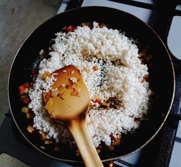 炒め野菜にお米を加えてシナモンライスを作るところ