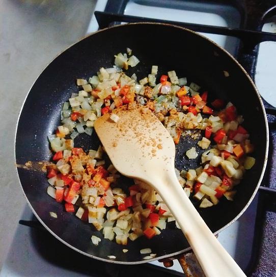 シナモンライス作りで野菜をフライパンで炒めてスパイスを加えるところ