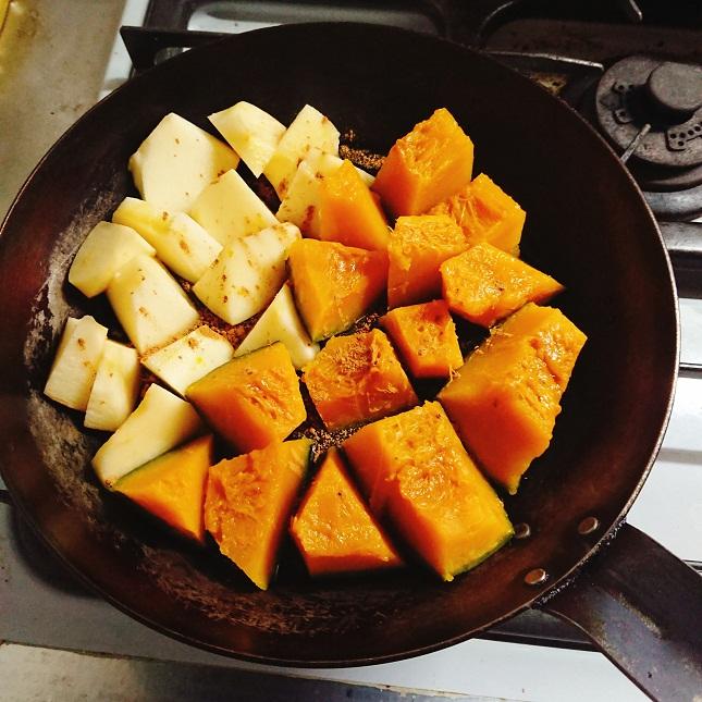 フライパンに並べた1口大のりんごとかぼちゃを加熱する