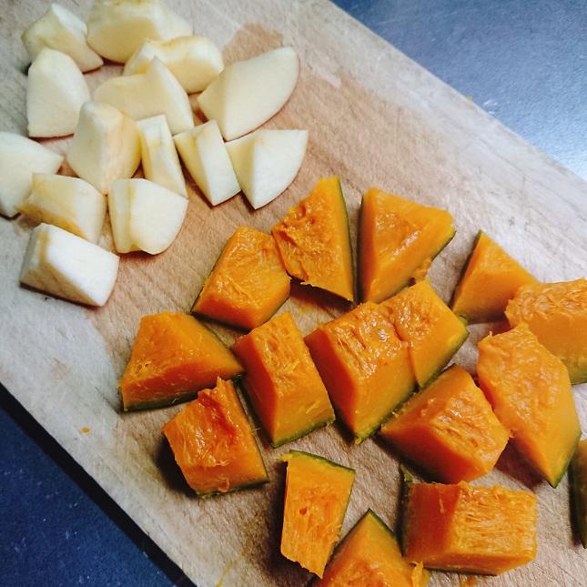 まな板の上に置いた、1口大に切ったりんご1/2個分とかぼちゃ1/8個分