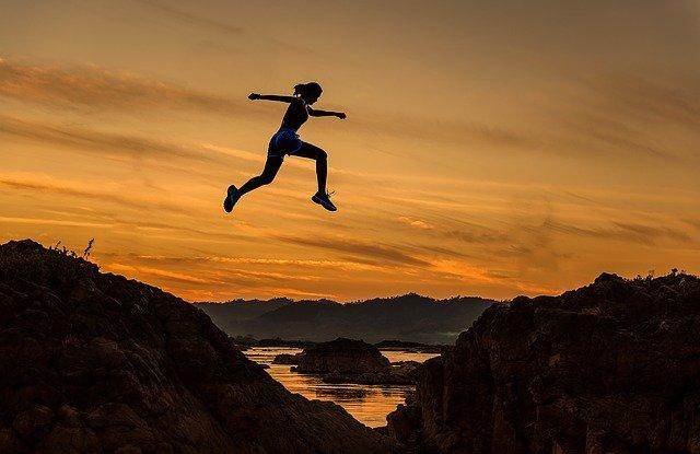 夕暮れの自然の中でアスレチック運動をする女性のシルエット