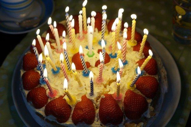 手頭栗のホールいちごケーキに沢山ろうそくを立てて火を灯した誕生日会