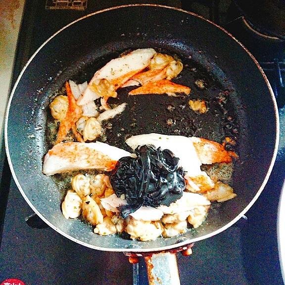 ガーリックバター、カニカマ、剥きあさりをフライパンで炒めたところに黒作りも追加投入
