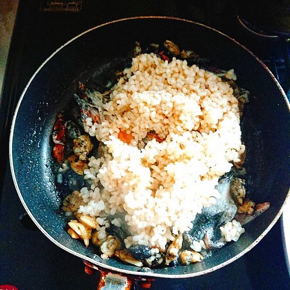 ガーリックバター、カニカマ、剥きあさりをフライパンで炒めたところに黒作りと白米も追加投入