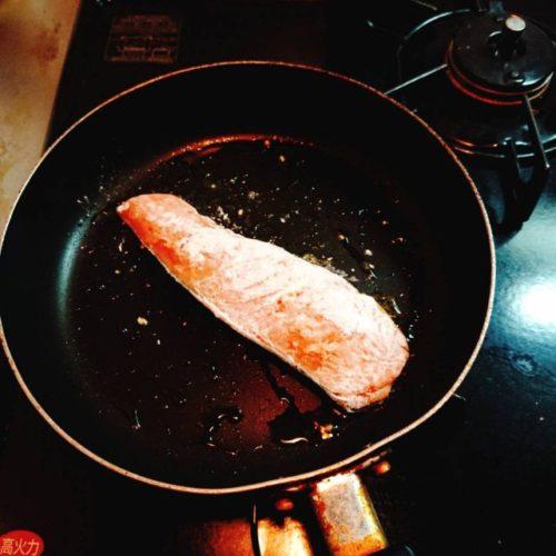 小麦粉をまぶした鮭をオリーブオイルで焼く