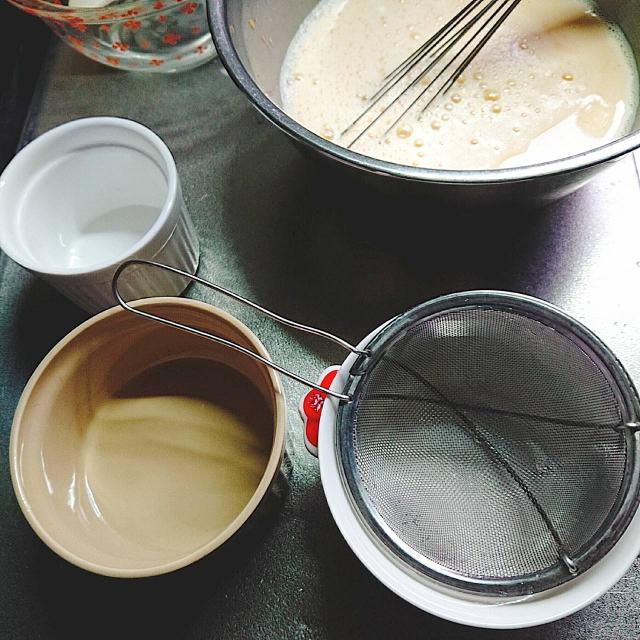 プリンの液を茶こしを使って容器に流し入れる